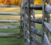 picture of split rail fence  - close up of a split rail fence with fall colors in the backgroung  - JPG