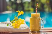 Mango Smoothies On The Background Of The Pool. Fruit Smoothie - Healthy Eating Concept. Close Up Of  poster