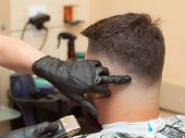 Making Modern Hairdo In Hairdressing Saloon, Close Up View. Stylist Cutting Hair With Clipper. Hands poster