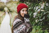 Beautiful Carefree Long Hair Asian Girl In Red Hat And Knitted Nordic Sweater In Autumn Nature Park, poster