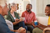 Senior and mature couples in conversation at home. Cheerful multiethnic group of people enjoying a c poster