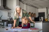 Old grandmother helping granddaughter while studying at home. Senior teacher helping little girl stu poster