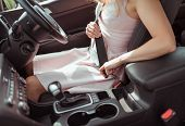 A Woman In A Car Sits Behind The Wheel, In The Summer In The City. Fastens Seat Belt, Right-hand Dri poster