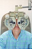 A Man Checks Eyesight In A Clinician Oculist. Man Checks His Vision On The Machine Checking Patient  poster