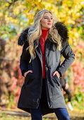 Modern Outfit For Youth. Girl In Warm Coat Stand In Park Nature Background Defocused. Woman Long Blo poster