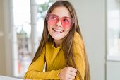 Beautiful young girl kid wearing pink heart glasses smiling looking side and staring away thinking. poster