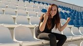 A Young Woman In Black Clothes With Long Hair Is Sitting On A Stadium Bleachers Alone And Rooting Fo poster