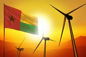 Guinea-bissau Wind Energy, Alternative Energy Environment Concept With Turbines And Flag On Sunset - poster