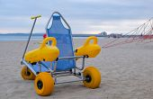 Beach Wheel Chair For Disabled Swimmers In The Beach On Blue Sea Background poster