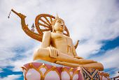 stock photo of piety  - Golden statue of Buddha sitting with beautiful skies above - JPG