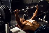 pic of execution  - very power athletic guy execute exercise press with weight in sport hall - JPG