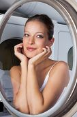 Closeup of beautiful young woman looking sideways through washing machine door