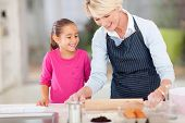 loving grandma baking cookies for granddaughter at home