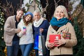 Portrait of happy senior woman holding Christmas presents with family standing in background at stor
