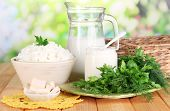 Fresh dairy products with greens on wooden table on natural background