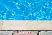 stock photo of heatwave  - No diving warning at the edge of a swimming pool - JPG
