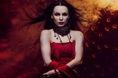 stock photo of pale skin  - Beautiful vampire woman in red dress with waving hair - JPG