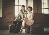 Beautiful vintage style young couple with suitcases on a train station