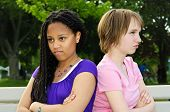 Two unhappy teenage girls sitting on bench