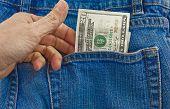 picture of twenty dollars  - A person pulling a twenty dollar bill out of a denim blue jean back pocket - JPG
