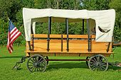 stock photo of covered wagon  - Horse drawn covered wagon with an American fkag - JPG