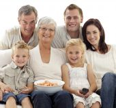 Постер, плакат: Портрет семьи смотрят телевизор и едят чипсы