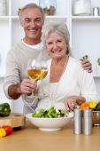 pic of elderly couple  - Happy senior couple eating a salad in the kitchen and drinkng wine - JPG