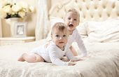 foto of baby twins  - Two baby boys playing on bed at home - JPG