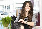 Happy hairdresser cutting hair in her salon
