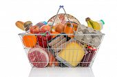 Studio shot of a shopping basket full of food including fresh fruit, vegetables, meat, pizza and dai