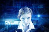 stock photo of spyware  - The word spyware and focused businesswoman against blue technology interface with circuit board - JPG