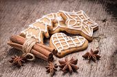stock photo of christmas spices  - Christmas iced gingerbread cookies with various spices on wood background - JPG