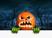 pic of scary haunted  - Demon pumpkin sign as an angry scary orange jack o lantern in a haunted dark autumn forest holding a blank sign with copy space as a symbol of a fun frightful seasonal holiday concept - JPG
