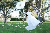 foto of levitation  - Floating Levitation Girl Outdoors With Book Pages Flying - JPG
