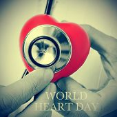 image of auscultation  - closeup of a doctor auscultating a red heart with a stethoscope and the text world heart day - JPG