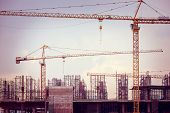 stock photo of construction crane  - Construction site with cranes on sky background retro tone image - JPG