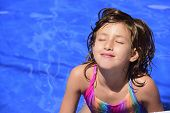stock photo of sunbathing  - Happy child relaxing in the pool sunbathing with eyes closed and copyspace - JPG