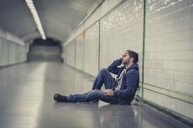 picture of underworld  - Young man abandoned lost in depression sitting on ground street subway tunnel suffering emotional pain sadness and looking destroyed and desperate leaning on wall alone - JPG