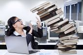 image of tasks  - Worried employee hold a pile of falling book in the office symbolizing task for work overtime - JPG
