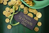 stock photo of leprechaun hat  - Happy St Patricks Day leprechaun hat with gold chocolate coins on vintage style green wood background - JPG
