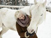 pic of feeding horse  - Attractive blond woman feeds a white horse overcast winter day - JPG