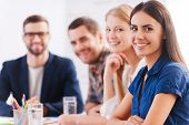 stock photo of casual wear  - Group of confident business people in smart casual wear sitting at the table together and smiling - JPG