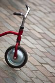 pic of tricycle  - Close up of a tricycle on a cobbled square - JPG