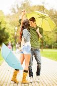 picture of dancing rain  - Young couple in love dancing in the park with umbrellas in hands - JPG