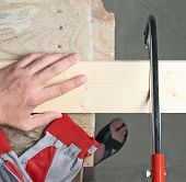 image of sawing  - Sawing wooden pine board with the hand saw indoor composition - JPG
