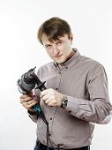stock photo of hand drill  - Young man with drilling machine in his hands ready to professional constructing work - JPG