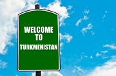 stock photo of turkmenistan  - Green road sign with greeting message WELCOME TO TURKMENISTAN isolated over clear blue sky background with available copy space - JPG
