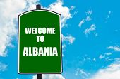 foto of albania  - Green road sign with greeting message WELCOME TO ALBANIA isolated over clear blue sky background with available copy space - JPG