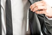 pic of jacket  - Businessman lifting aside his jacket by the lapel in order to access a pen in an inner pocket of the jacket or breast pocket of his shirt close up view of his hand and chest - JPG