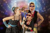 picture of rockabilly  - Rockabilly woman with her daughters having fun posing with vintage microphone in 1950 - JPG